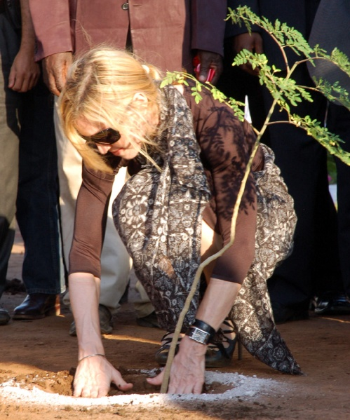 Madonna plants a tree at the ground designated for the school construction